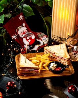 Club sandwich with salami served with french fries mayonnaise and ketchup