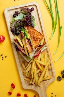 Club sandwich with side greenery and fries
