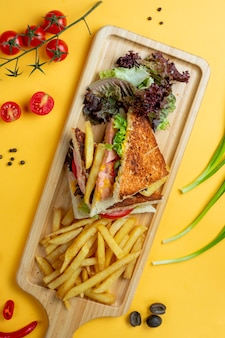 Club sandwich with side herbs and fries _