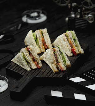 Club sandwiches on a black wooden board