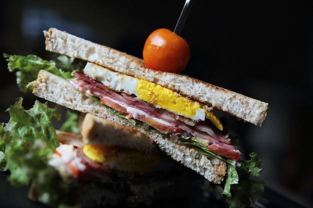 Клубные бутерброды на деревянном фоне с мистическим светом