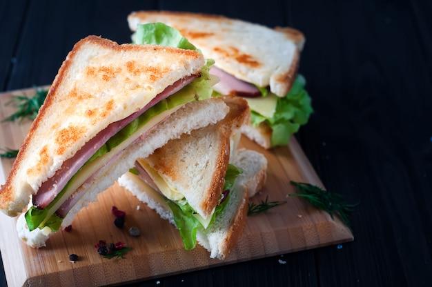 Клубные сэндвичи на фоне дерева