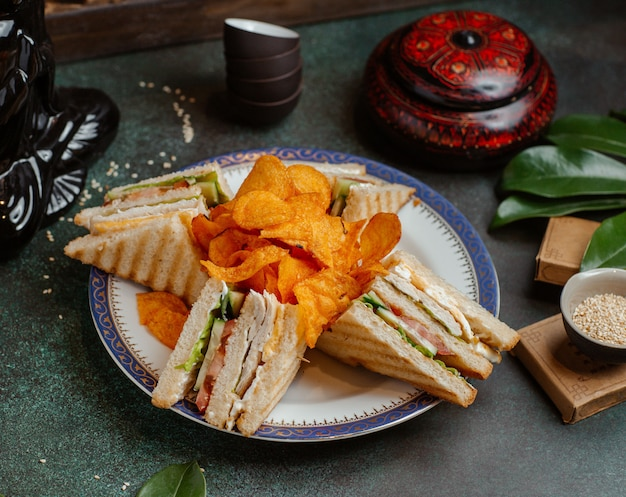 Club sandwiches and potato chips in a plate.
