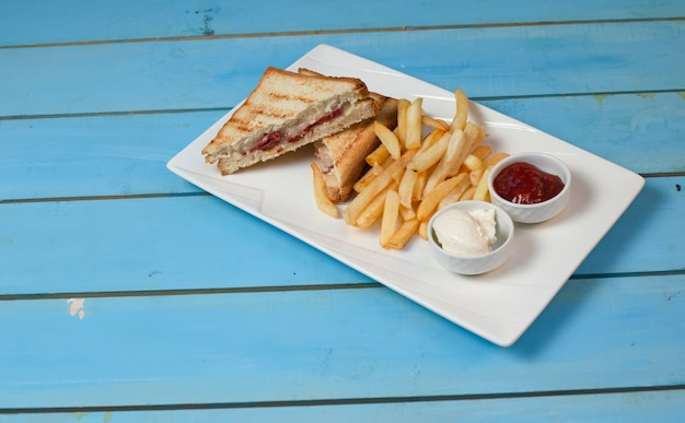 Club sandwiches served with fried potatoes in white plate with ketchup and mayonnaise on blue table