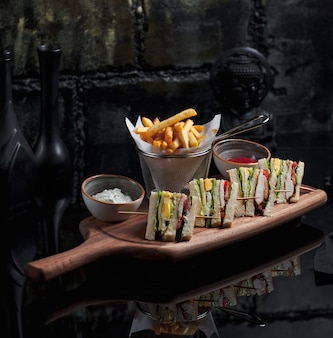 Club sandwiches set with fries in metallic basket