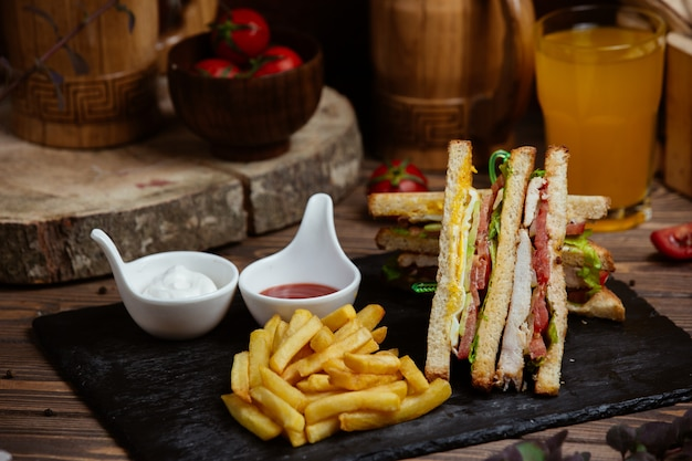 Club sandwiches in toast with french fries and sauces.