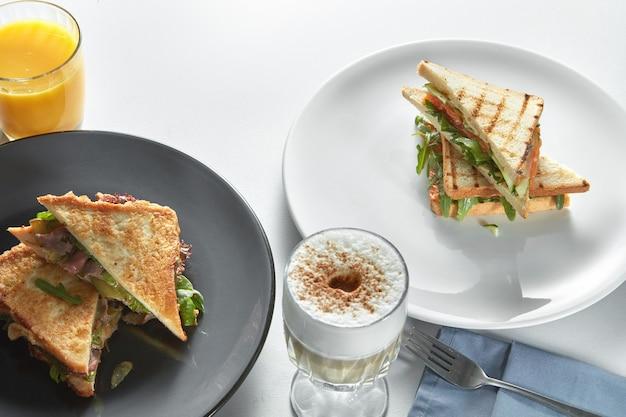 テーブルの上にさまざまなフィリングとカプチーノのクラブサンドイッチ