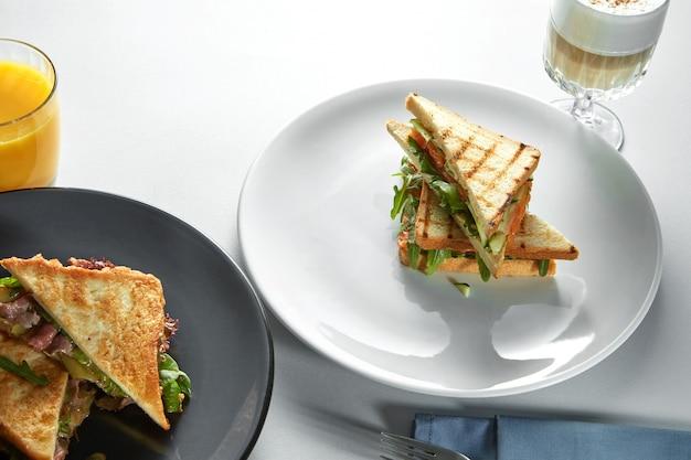 テーブルの上にさまざまな詰め物のクラブサンドイッチ