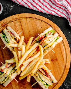 Club sandwiches with french fries on a wooden round board.