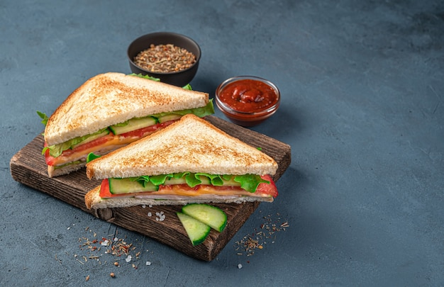 소스와 향신료를 곁들인 진한 파란색 배경에 햄, 치즈, 신선한 야채를 곁들인 클럽 샌드위치. 측면 보기, 복사 공간입니다.