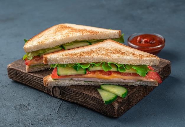 ダークブルーの背景にハムチーズと野菜のクラブサンドイッチ