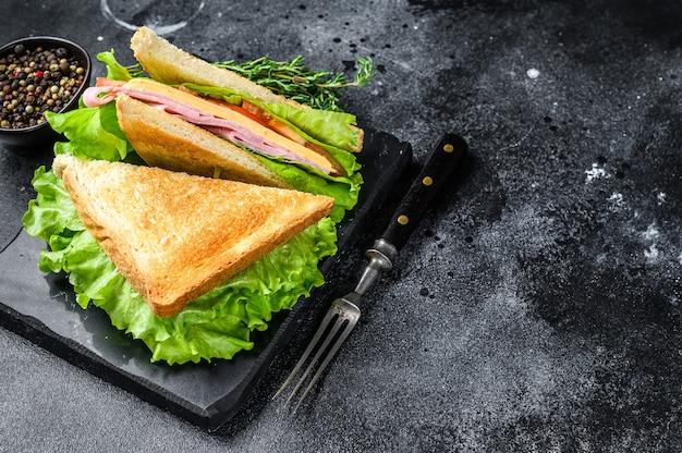 木製のまな板の上にポークハム、チーズ、トマト、レタスのクラブサンドイッチ。黒の背景。上面図。スペースをコピーします。