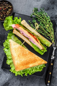 Клубные бутерброды со свининой, сыром, помидорами и салатом на деревянной разделочной доске. черный фон. вид сверху.