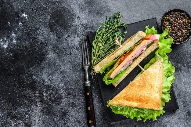 木製のまな板にポーク ハム、チーズ、トマト、レタスのクラブ サンドイッチ。