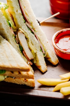 Club sandwiches with potatoes and red sauce.