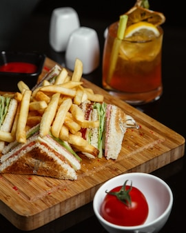 Club sandwiches with potatoes on a wooden board with tomato and lemonade.