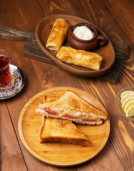 Club sandwiches with salami, bacon and blinchik served with yogurt in wooden plate with tea.