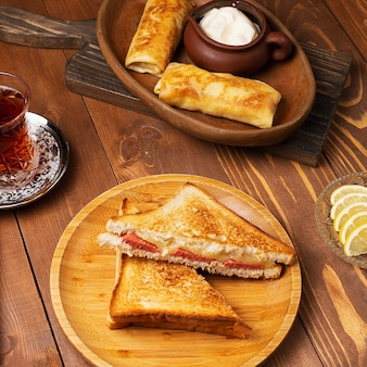Club sandwiches with salami, bacon and blinchik served with yogurt in wooden plate with tea