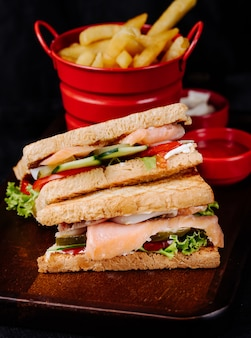 Club sandwiches with vegetable and ham, with french fries.