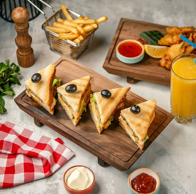 Club sandwiches on a wooden board with fries and orange juice.