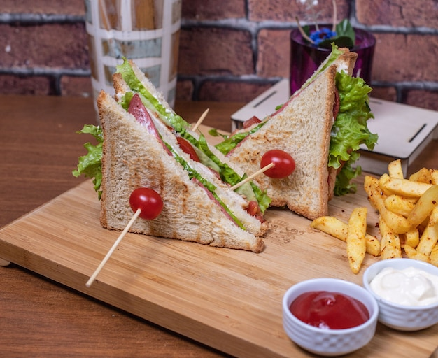 Club sandwiches on a wooden board with sauces.