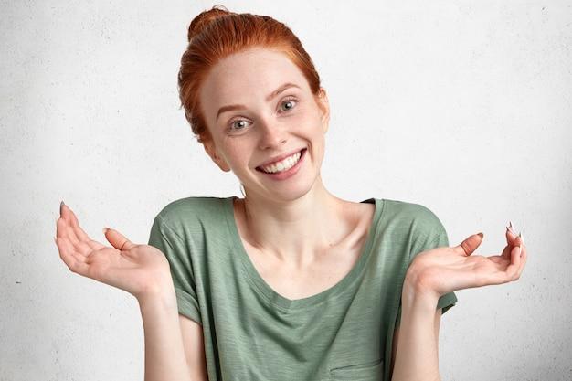 Невежественная очаровательная молодая счастливая рыжая женщина с мягкой чистой кожей и приятной улыбкой, пожимая плечами, не может принять решение, одетая небрежно изолированно на белом