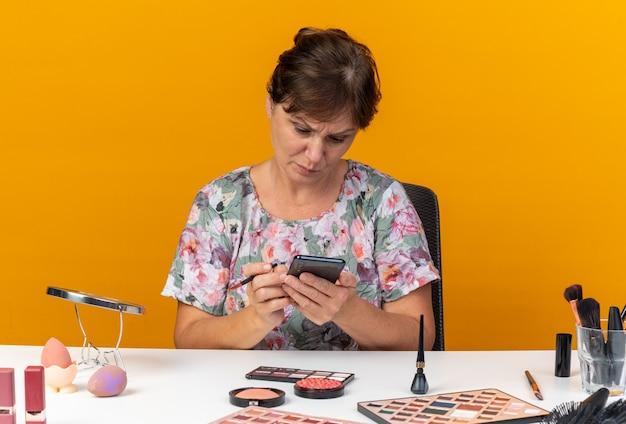 메이크업 브러쉬를 들고 주황색 벽에 격리된 전화기를 보고 복사 공간이 있는 화장 도구를 들고 테이블에 앉아 있는 단서 없는 성인 백인 여성