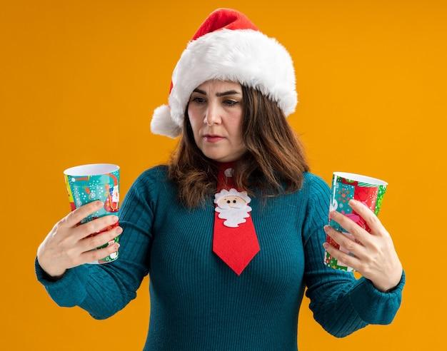サンタの帽子とサンタのネクタイを保持し、コピースペースとオレンジ色の背景に分離された紙コップを見て無知な大人の白人女性