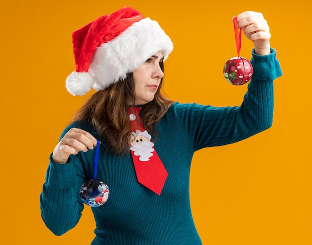 Clueless adult caucasian woman with santa hat and santa tie holding and looking at glass ball ornaments isolated on orange wall with copy space