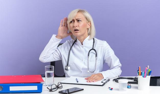 聴診器を持った医療ローブの無知な成人女性医師が、コピースペースのある紫色の壁に孤立して聞こえるように手を耳に近づけてオフィスツールを使って机に座っています。