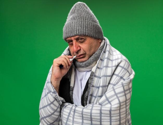 首の周りにスカーフを身に着けている無知な大人の病気の白人男性は、コピースペースのある緑の壁に隔離された彼の口に温度計を保持している格子縞に包まれた冬の帽子をかぶっています