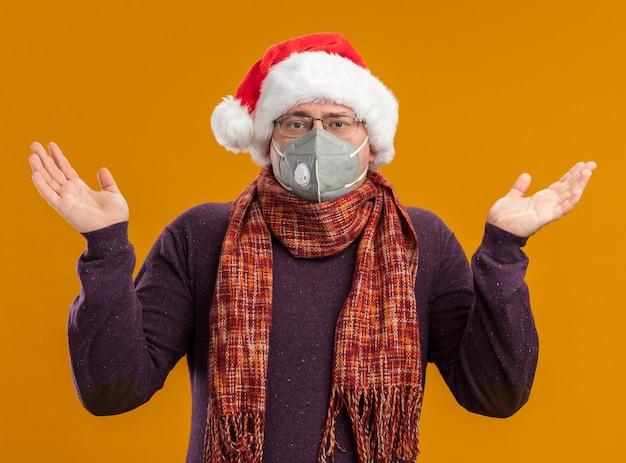 Uomo adulto senza tracce che indossa occhiali maschera protettiva e cappello della santa con la sciarpa intorno al collo che guarda l'obbiettivo che mostra le mani vuote isolate su fondo arancio