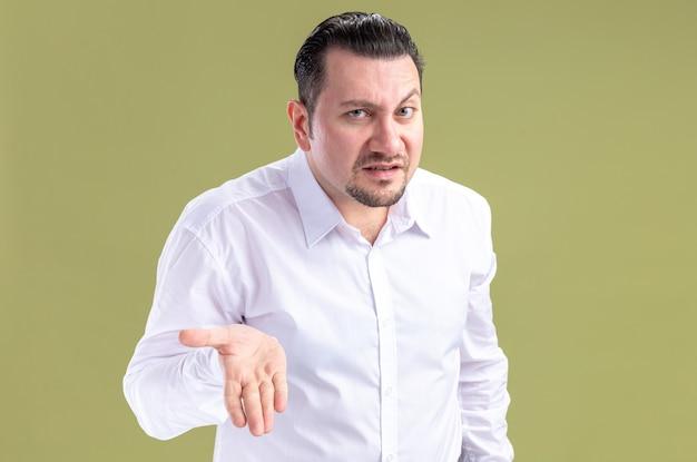 Uomo d'affari slavo adulto senza indizi che tiene la mano aperta e guarda la telecamera