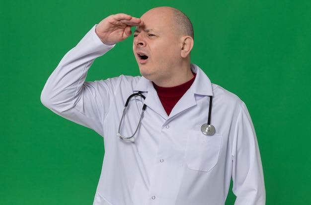 옆을 보고 있는 그의 이마에 손바닥을 유지하는 청진기가 있는 의사 유니폼을 입은 단서 없는 성인 슬라브 남자