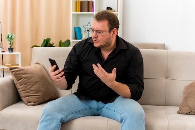 광학 안경에 우 둔 성인 슬라브 남자는 안락 의자에 앉아 거실 내부의 전화를보고 있습니다.
