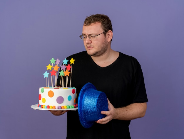 Clueless adult slavic man in optical glasses holds blue party hat and birthday cake