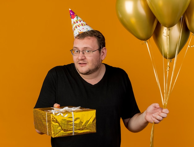 Clueless adult slavic man in optical glasses wearing birthday cap holds helium balloons and gift box