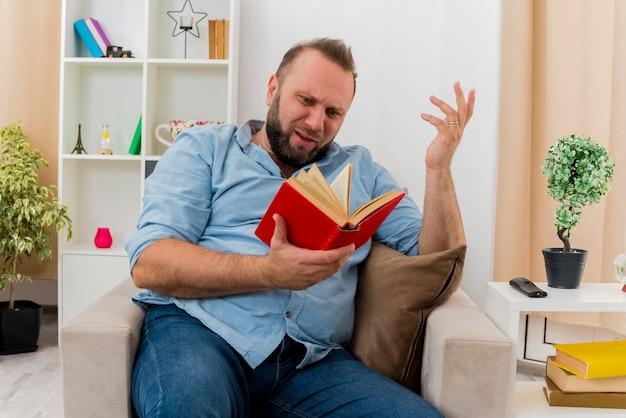 Невежественный взрослый славянский мужчина сидит на кресле, подняв руку, держа и глядя на книгу в гостиной