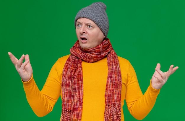 冬の帽子と首にスカーフを持った無知な大人のスラブ人が手を開いたまま横を見て