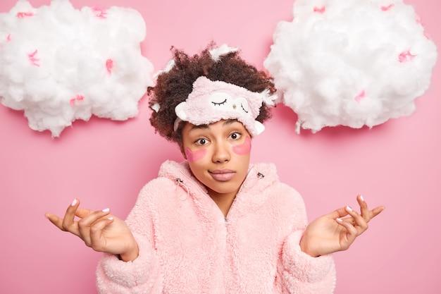 無知なアフリカ系アメリカ人の女性が柔らかいパジャマを着て横に手のひらを広げ、ピンクの壁に対して躊躇する表情のポーズをとって何をすべきかを決めようとします