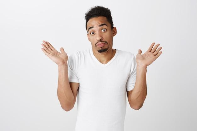 無知で肩をすくめて無知で混乱しているアフリカ系アメリカ人の男、何も知らない