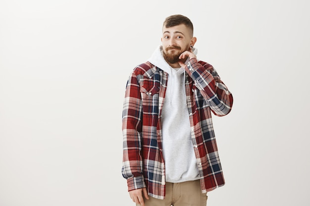 Clueless awkward hipster guy scratching beard and looking guilty