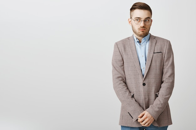 Clueless awkward male employee looking away and looking guilty, hiding something