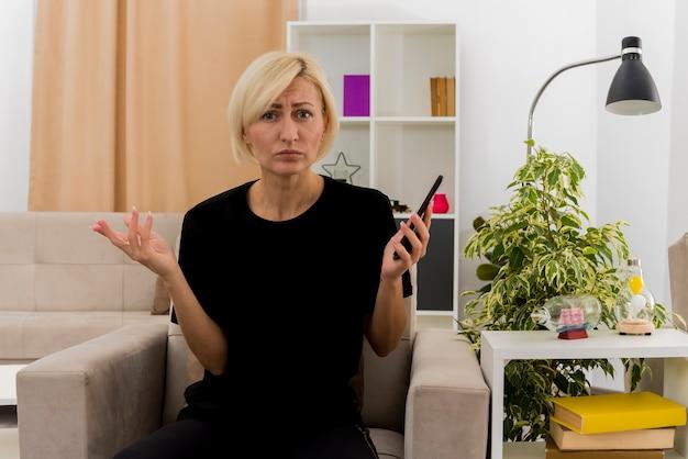 無知な美しい金髪のロシアの女性は、リビングルームの中で電話を保持している肘掛け椅子に座っています