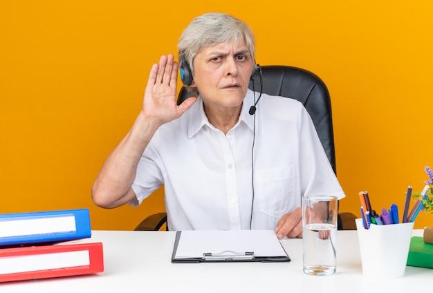 Operatore di call center femminile caucasico senza indizi sulle cuffie seduto alla scrivania con strumenti da ufficio tenendo la mano vicino al suo orecchio cercando di sentire isolato sul muro arancione