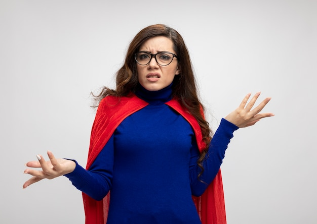 Clueless caucasian superhero girl in optical glasses with red cape holds hands open on white