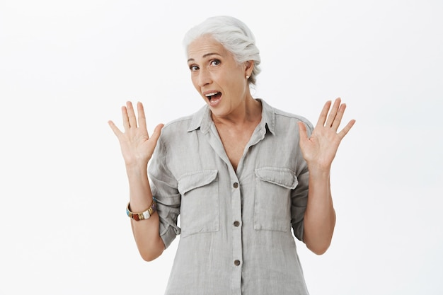 Clueless cheerful old lady raising hands up uninvolved, being confused