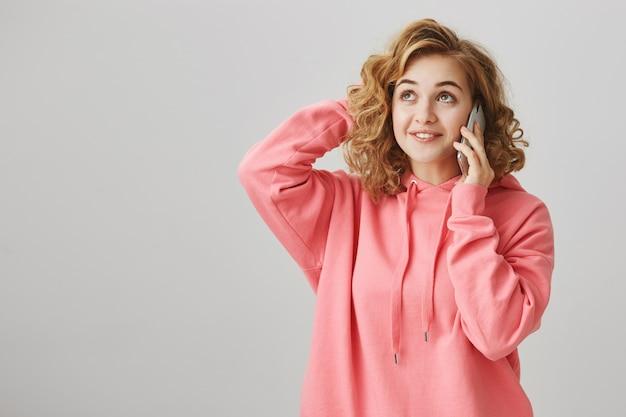 Бестолковая милая девушка почесать голову, задумавшись, как разговаривает по телефону