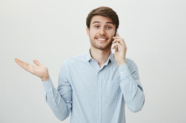 剛毛が電話で話していると肩をすくめて無知なかわいい男