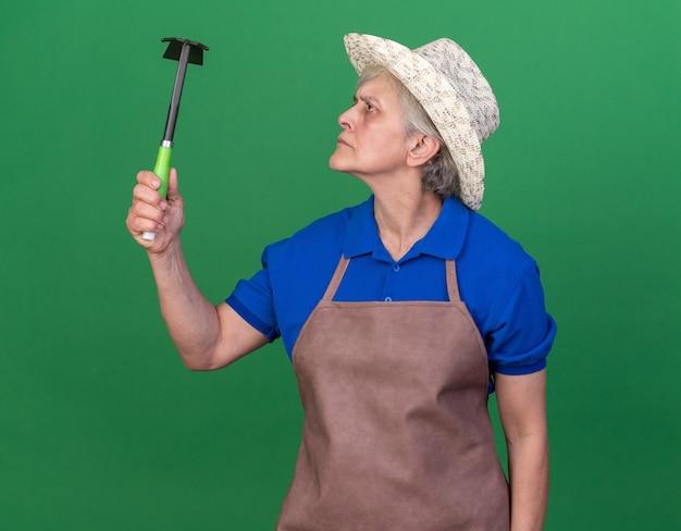 ガーデニング帽子をかぶって鍬熊手を見て無知な年配の女性の庭師
